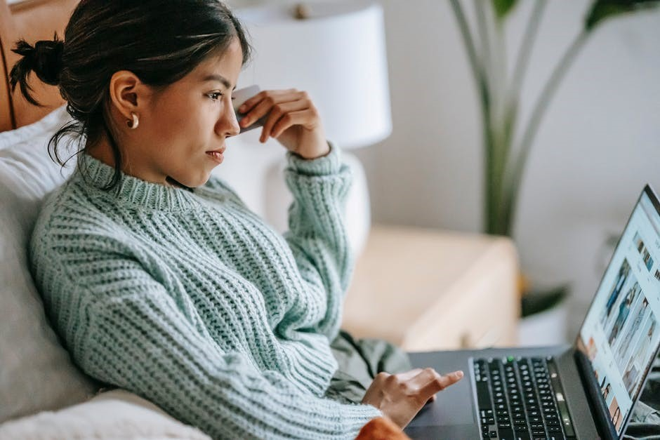 A female customer shops online while sitting on her couch.