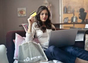 A woman sitting on her couch holding a credit card, shopping online.