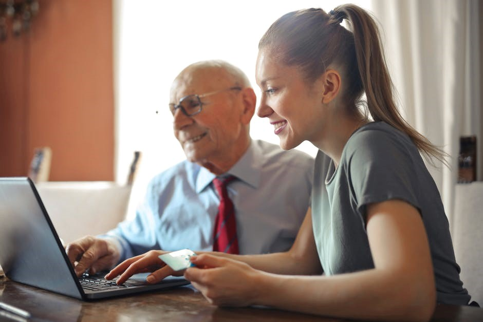 A woman and her elderly father shopping online through a website